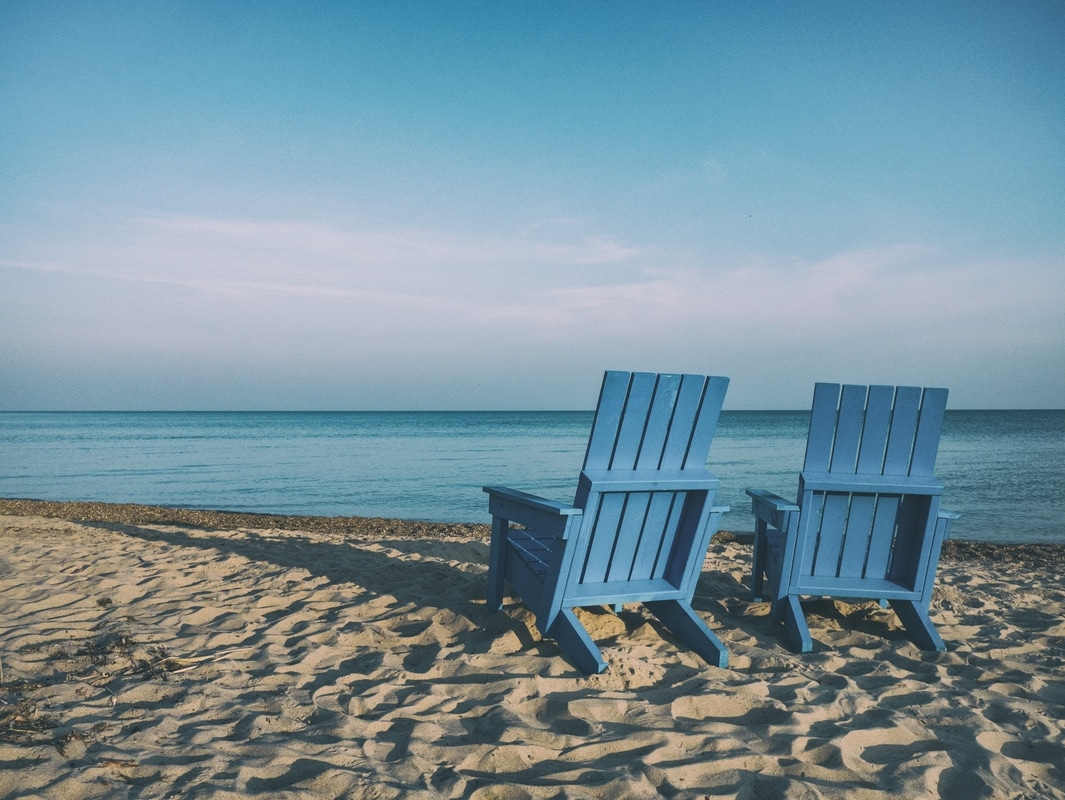 blue wooden chairs on sandy beach