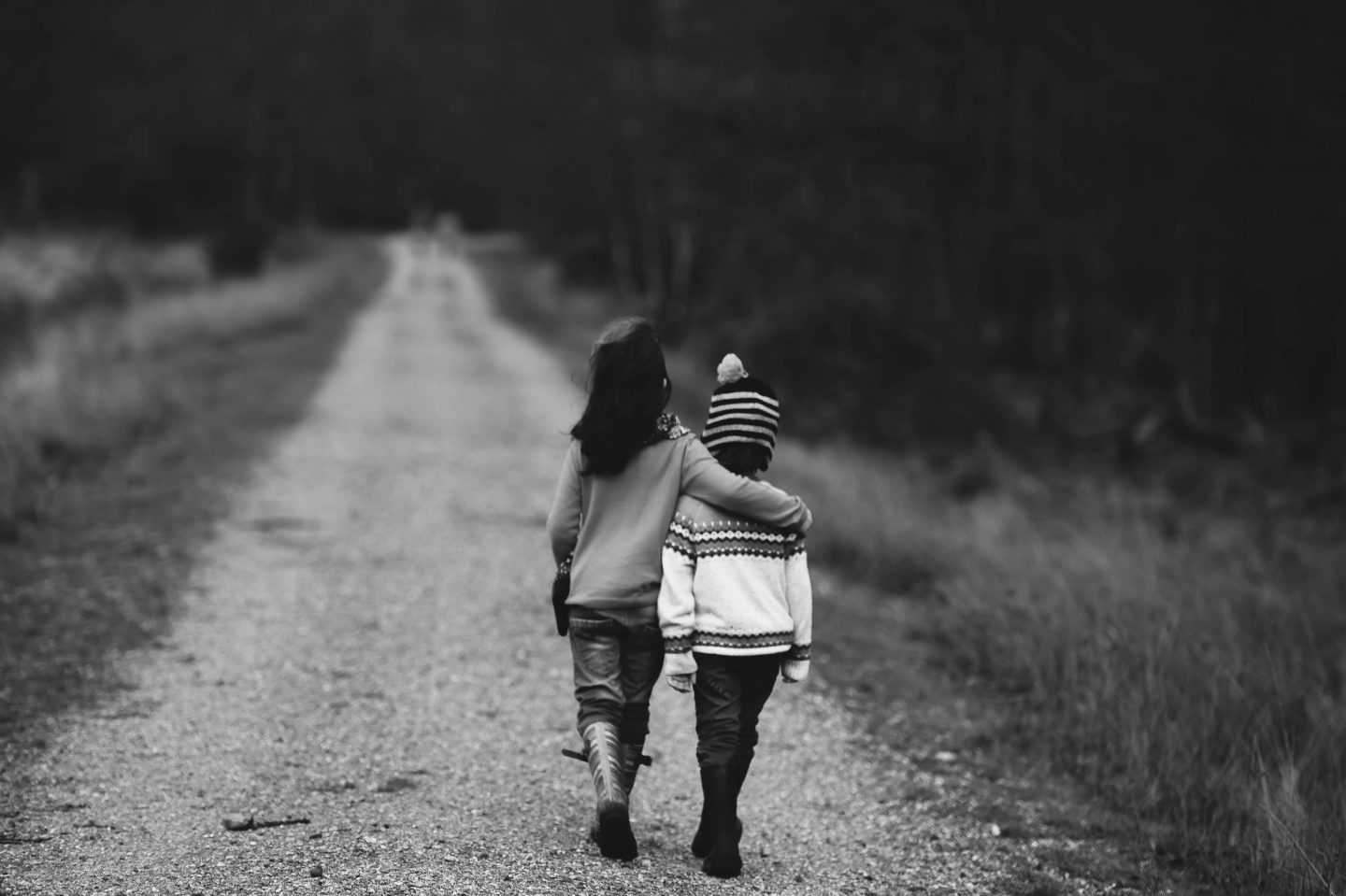 two kids side hugging each other walking away from camera